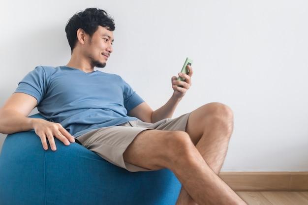 幸せな男は、ビーンバッグに座ってリラックスしながらスマートフォンを使用しています。