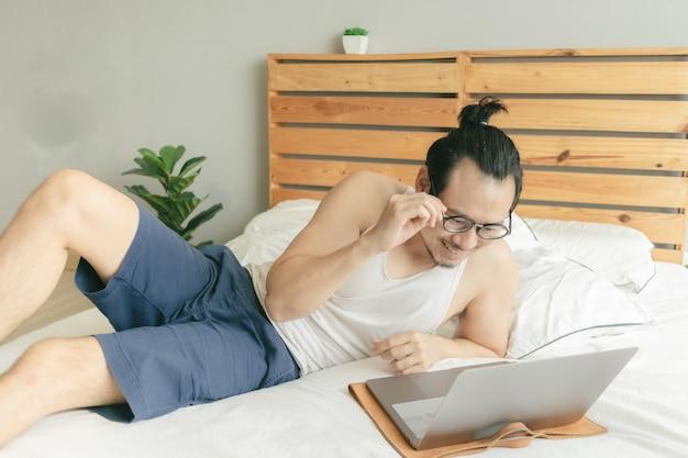 幸せな男は非常に居心地の良いカジュアルな服と髪で家で働いています。