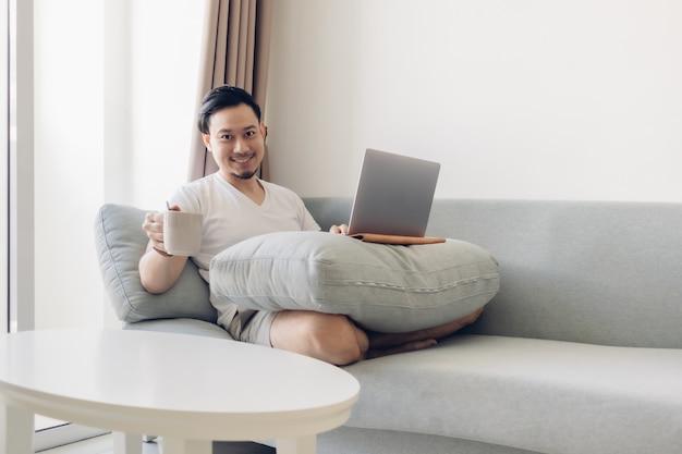 幸せな男は、自宅での仕事の概念でソファーに取り組んでいます。