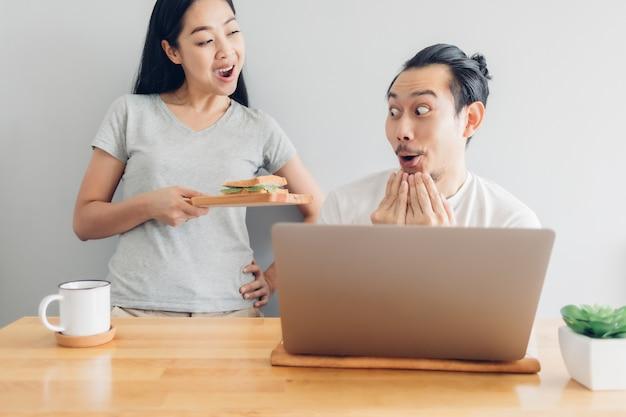 幸せな男は家から仕事の概念で彼の妻のサポートとオンラインで働いています。