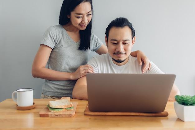 幸せな男は彼の妻のサポートでオンラインで働いています