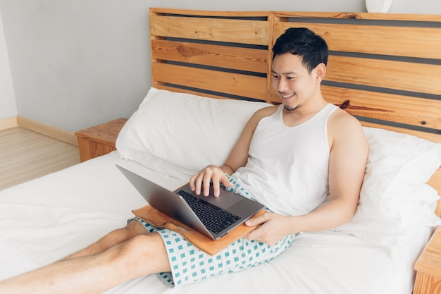 Happy man is working with his laptop on his bed. concept of freelancer successful lifestyle.