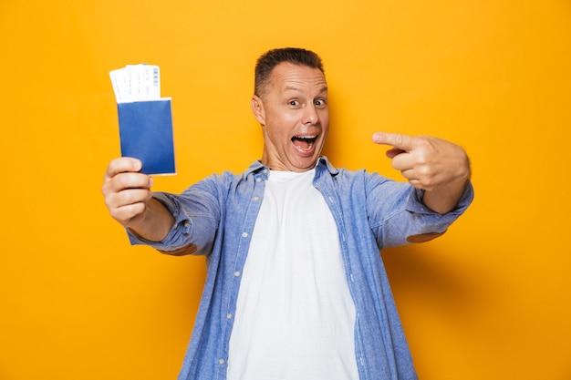 Счастливый человек, изолированные над желтой стеной, держащей паспорт.