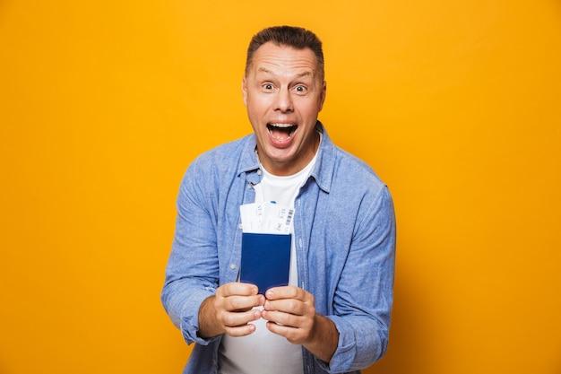 Счастливый человек, изолированные на желтой стене, холдинг паспорт.