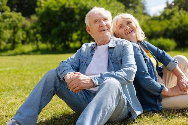 Счастливый человек держит улыбку на лице, глядя вверх и держа руки вместе на коленях