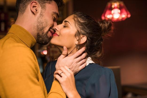 Happy man kissing cheerful woman