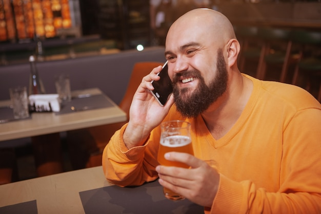 Happy man laughing, drinking beer and talking on the phone at the bar, copy space. good news concept