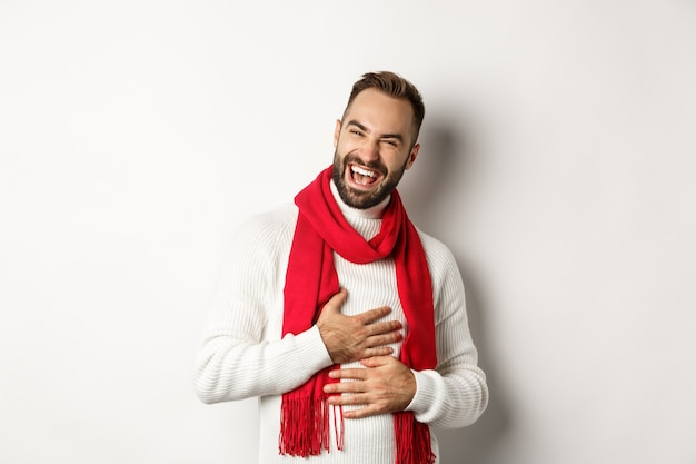 Uomo felice che ride e tocca la pancia, ridacchia da uno scherzo divertente, in piedi in maglione invernale e sciarpa rossa, sfondo bianco.