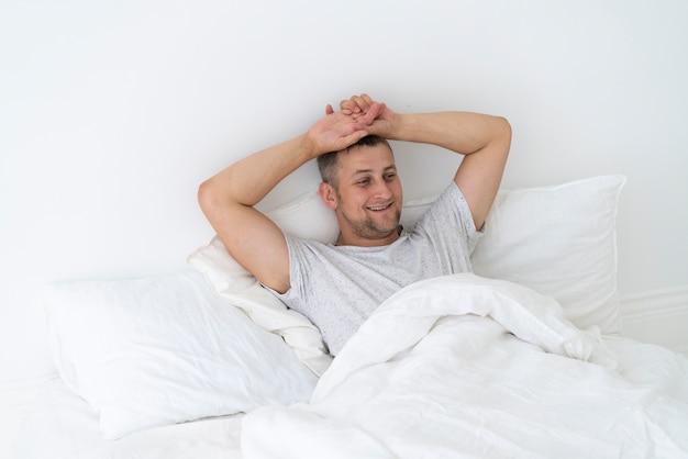 幸せな男が寝室に敷設