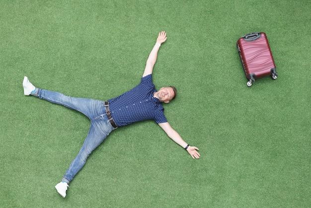 행복 한 사람 가방 평면도와 녹색 잔디에 누워