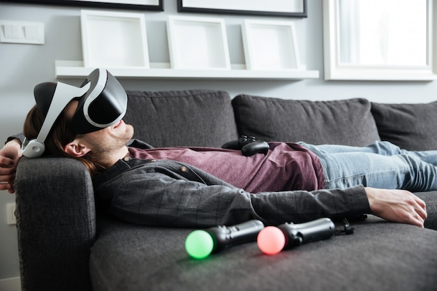 Happy man lies on sofa at home wearing 3d glasses