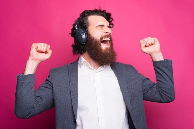 幸せな男は音楽を聴き、両手を上げて元気を出して聞く