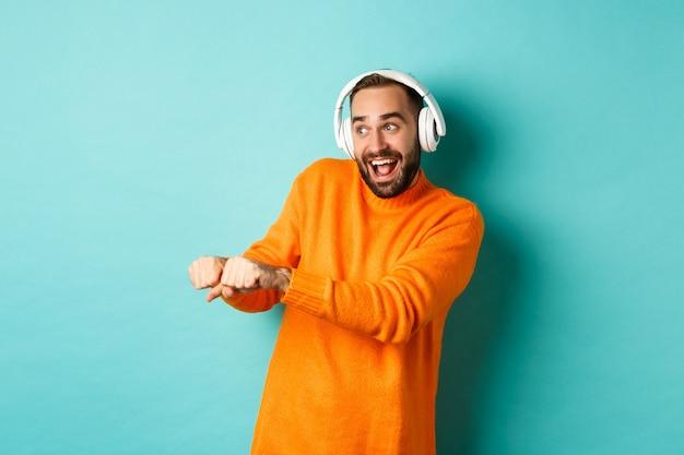 행복 한 사람 헤드폰에서 음악을 듣고 청록색 배경 위에 서 재미 춤. 공간 복사