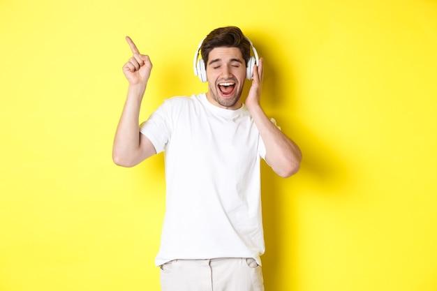헤드폰을 끼고 음악을 듣고 있는 행복한 남자, 노란색 배경 위에 서서 검은 금요일 프로모션 제안을 손가락으로 가리키고 있습니다.