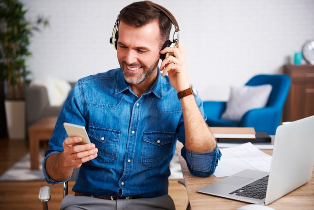 Happy man listening to music and using mobile phone