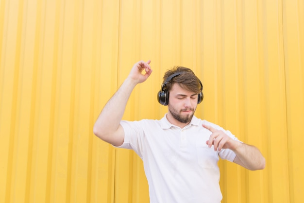 A happy man listens to music on headphones and smiles on a yellow wall.