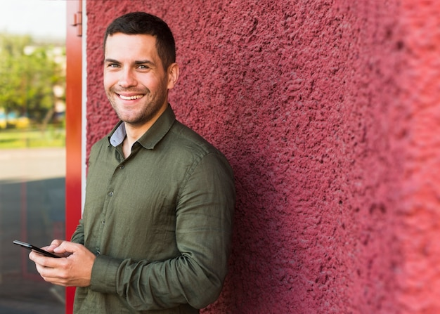 Happy man looking at camera while holding cellphone near red wall