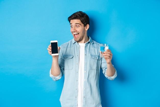 Uomo felice che guarda eccitato allo schermo del telefono cellulare, con in mano un bicchiere d'acqua, in piedi su sfondo blu.