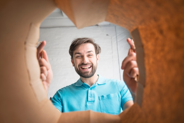 Happy man looking inside paper bag