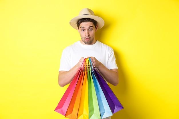 Счастливый человек, глядя удивлен на хозяйственные сумки, покупая сувениры в отпуске, стоя на желтом фоне.