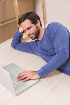 Happy man lying on floor using laptop