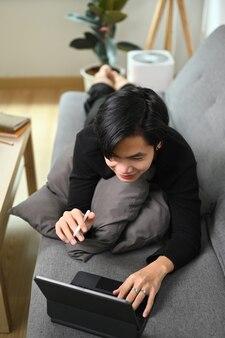 Счастливый человек, лежа на удобном диване и с помощью компьютерного планшета.