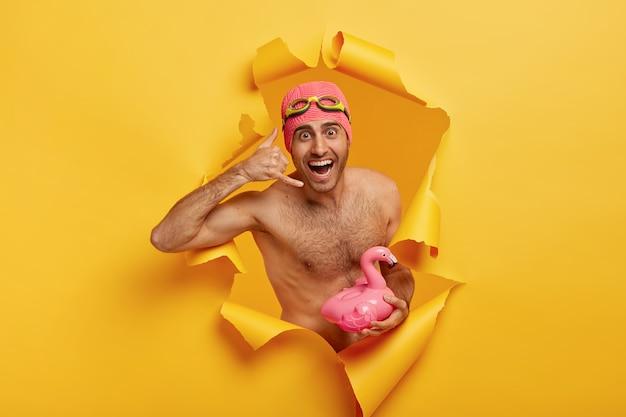 행복한 남자가 전화 제스처를하고, 수영복과 고글을 착용하고, 벌거 벗은 몸통으로 서 있고, 분홍색 플라밍고를 들고, 기분이 좋습니다.
