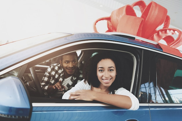 Happy man makes gift to woman buying dream car.
