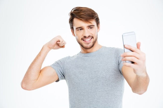Happy man making selfie photo on smartphone and showing his biceps isolated on a white background