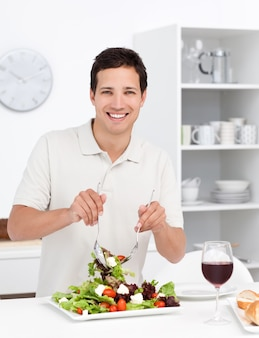 Happy man mixing a salad standing in the kitchen