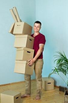 幸せな男は物を開梱して家に移動します。男は手に箱を持って微笑む。引っ越し、新しい住宅、住宅ローンの概念。独身者がアパートを装備