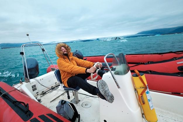 아이슬란드 joculsarlon의 얼음 석호에서 보트를 타고 있는 행복한 남자. 얼음이 바다에 닿기 위해 내리막으로 내려가는 유명한 아이슬란드 얼음 석호. 유명한 목적지를 조사하기 위해 걷고 배를 타는 사람들.