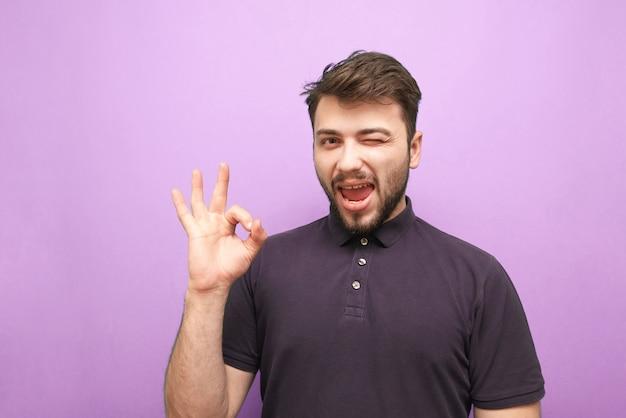 紫色の背景の幸せな男はサインokに微笑む