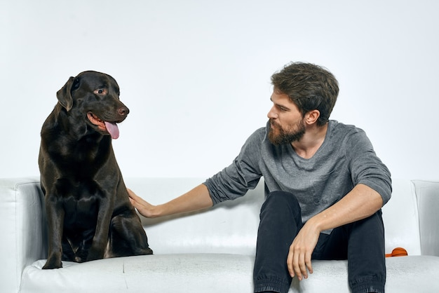 Счастливый человек на диване со своей собакой, изоляция и карантин с собакой дома