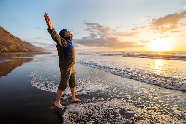 ビーチで日の出の幸せな男。旅行と感情の概念
