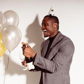 Uomo felice che apre una bottiglia di champagne