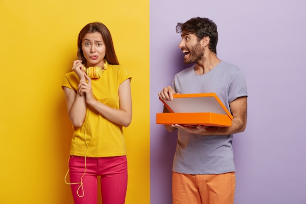 Happy man opens box with surprise, shows something to girlfriend who has unhappy puzzled look, frowns face, wears yellow t shirt and pink trousers, headphones around neck.