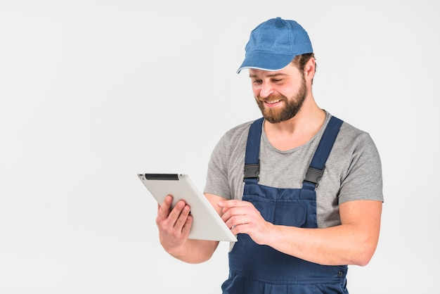 Happy man in overall using tablet