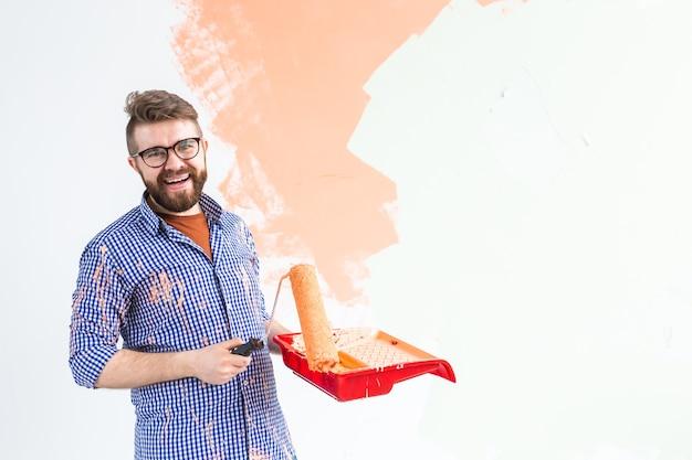새 집에 페인트 롤러와 인테리어 벽 그림 행복 한 사람. 롤러에 페인트를 적용하는 남자는