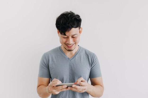 Счастливый человек играть в мобильную онлайн-игру на белом фоне
