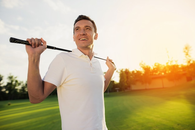 Happy man player in white holding golf club.