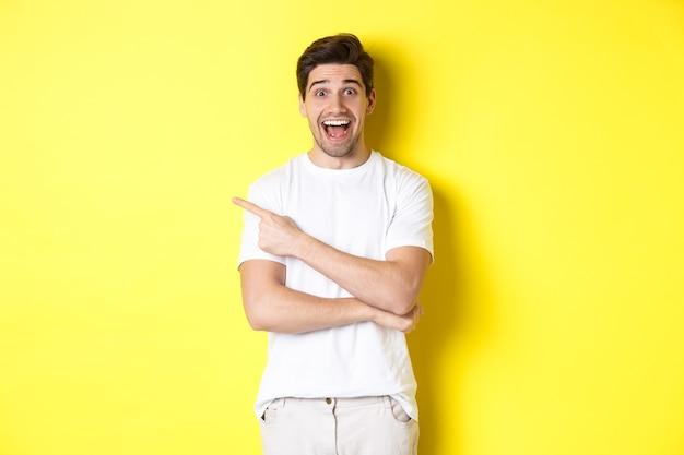 Uomo felice che punta il dito a sinistra, mostrando la pubblicità sullo spazio della copia, sorridendo divertito, in piedi in abiti bianchi su sfondo giallo.