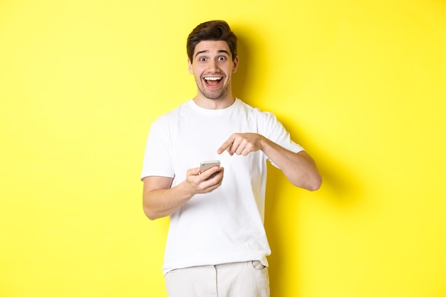 Happy man pointing at smartphone to show promo, check out internet offer, standing over yellow