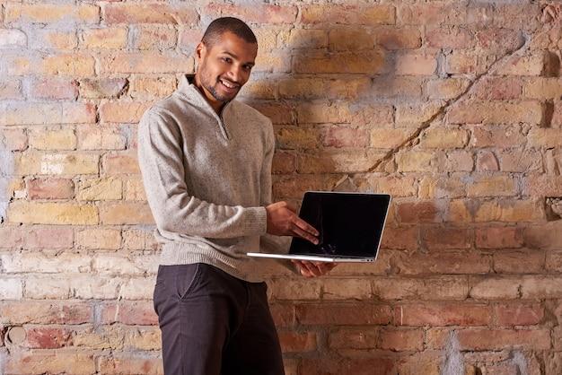 ノートパソコンを指している幸せな男