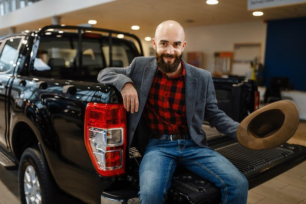 Happy man poses in the back of new pickup truck in car dealership. customer in vehicle showroom, male person buying transport, auto dealer business