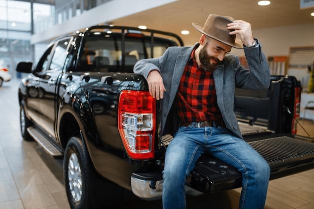 幸せな男は、新しいピックアップトラックの後ろでポーズをとる