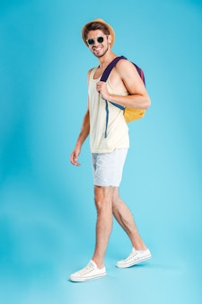 Happy man posing with backpack and sunglasses