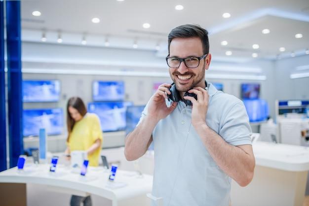 ハイテクストアでイヤホンでポーズをとって幸せな男。技術ショッピングのコンセプトです。