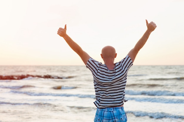 Happy man raises his arms up against the sea