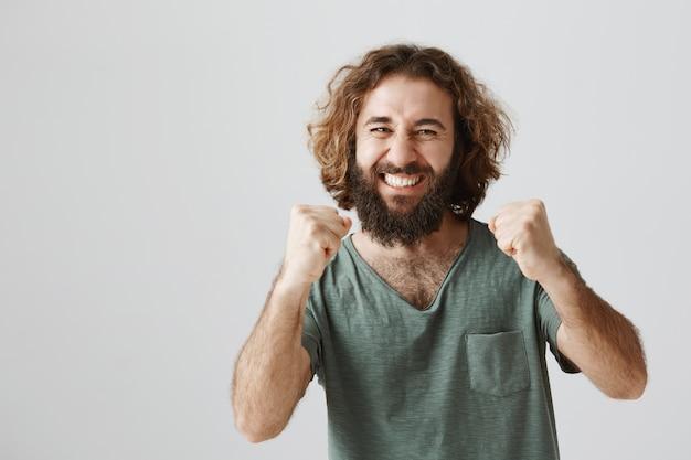 喜んで拳を上げて勝利し、良いニュースを祝う幸せな男